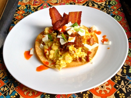 Breakfast tostada with eggs, bacon, onions, queso fresco, scallions, salsa, and Cholula hot sauce. The corn tortilla was fried just before making the eggs.
