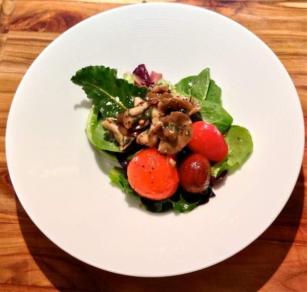 Marinated mushroom and tomato salad with baby romaine lettuce, beet greens, and a white Balsamic vinaigrette. The mushrooms are hen of the woods that have been blanched in salted, boiling water and marinated with sherry vinegar, olive oil, kosher salt, cracked black pepper, coriander seeds, fennel fronds, and thyme.
