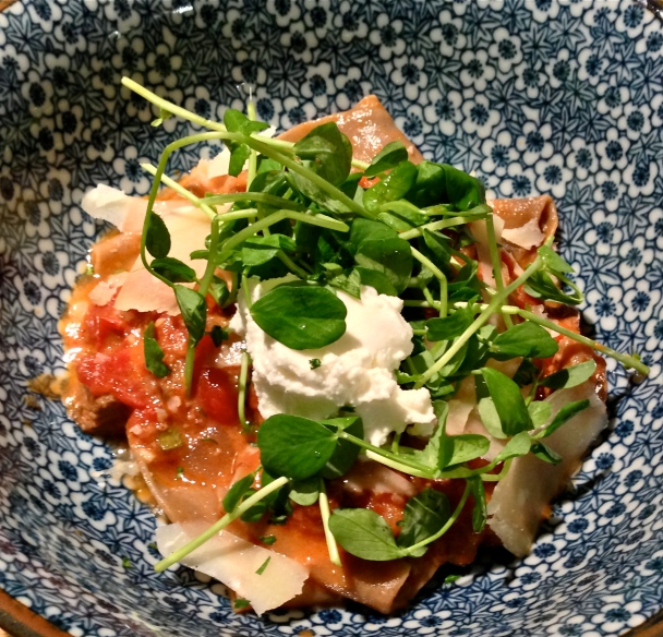 Black Garlic Pappardelle with Lamb Ragù alla Bolognese, garnished with pea shoots, shaved Parmesan, and ricotta.