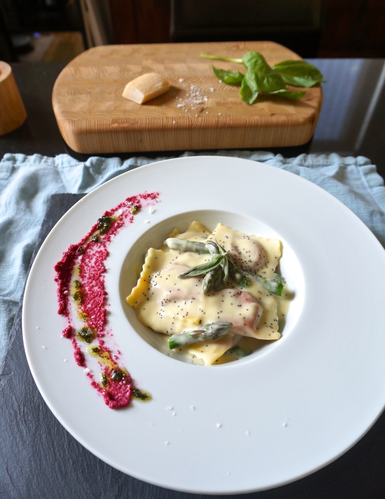 Beet, sage, and ricotta agnolotti in a zucchini crema with asparagus and poppy seeds. Orange zest in the agnolotti filling gives this dish a nice floral and citrus note.